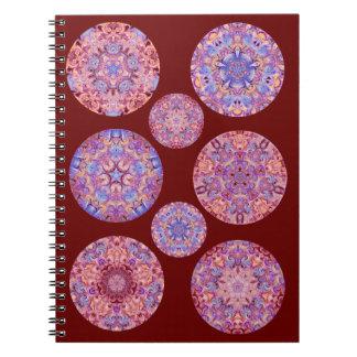 Cuaderno rojo oscuro con los círculos del caleidos