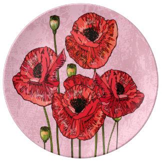 Cuatro amapolas rojas bonitas en rosa platos de cerámica