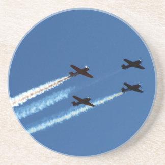 cuatro aviones que vuelan con el cielo azul de los posavasos para bebidas