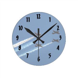cuatro aviones que vuelan con el cielo azul de los reloj redondo mediano