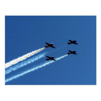 cuatro aviones que vuelan con el cielo azul de los postal