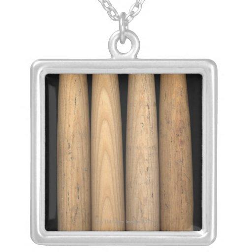 Cuatro bates de béisbol viejos en fondo negro colgante cuadrado