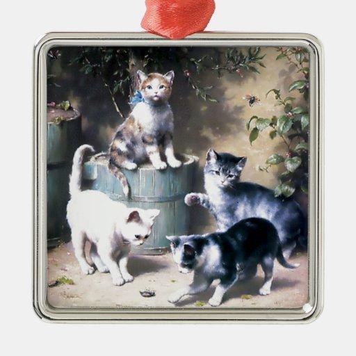 Cuatro gatitos que juegan con la pintura de los ornamento para reyes magos