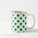 Cuatro tréboles de la hoja en verde taza de café