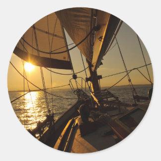 Cubierta del velero, dirigiendo en el sol poniente pegatina redonda