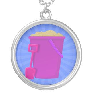 Cubo púrpura por completo de arena y de espada colgante redondo