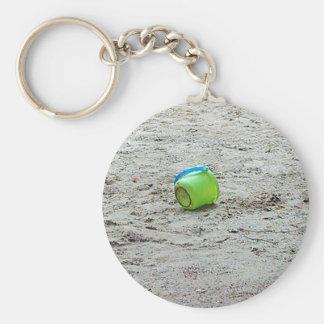 Cubo verde perdido en arena en la playa del verano llavero redondo tipo pin