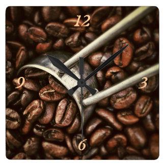 Cucharada de los granos de café reloj cuadrado