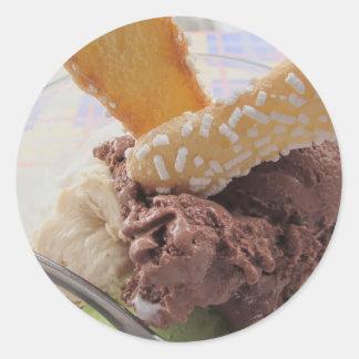Cucharadas mezcladas del helado con las galletas pegatina redonda
