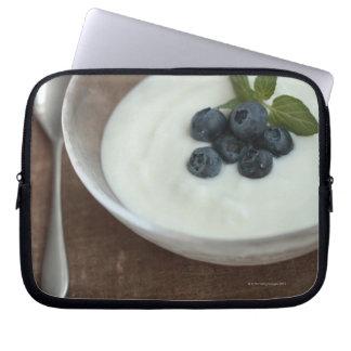 Cuenco de yogur con el arándano en la tabla manga portátil