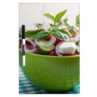 Cuenco verde con la ensalada vegetal en mantel tableros blancos