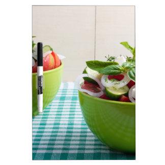 Cuenco verde dos con la ensalada vegetariana pizarras blancas de calidad