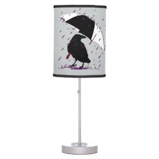 Cuervo en la lámpara púrpura de la lluvia