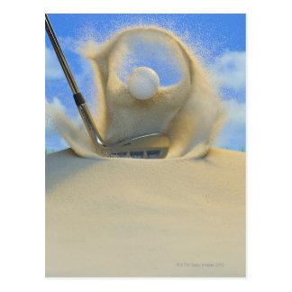 cuña de arena que golpea una pelota de golf fuera tarjeta postal