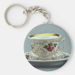 Cup and saucer with colorful flower designs on it. key chains