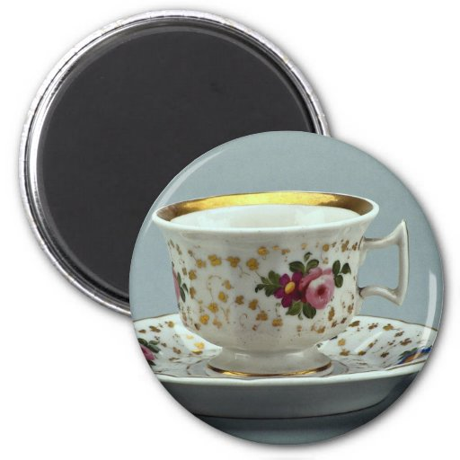 Cup and saucer with colorful flower designs on it. fridge magnets