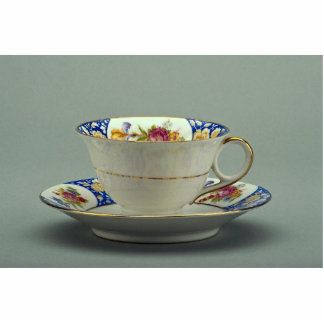 Cup and saucer with colorful flower designs on it. standing photo sculpture