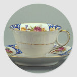 Cup and saucer with colorful flower designs on it. stickers