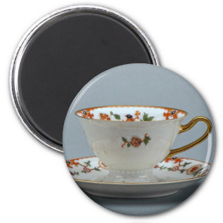 Cup and saucer with colorful flowers on it. 2 inch round magnet