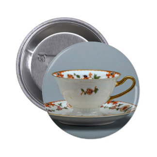 Cup and saucer with colorful flowers on it. pinback button