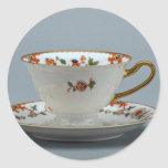 Cup and saucer with colorful flowers on it. round stickers