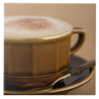 Cup of cappuccino with cocoa powder tile