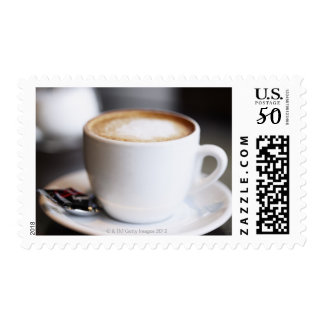 cup of coffee latte on table, close-up postage