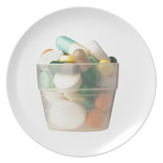 Cup of pills dinner plate
