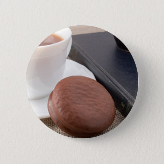 Cup with hot cocoa and chocolate cake button