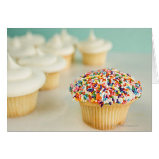 Cupcakes focus on one in front with greeting cards