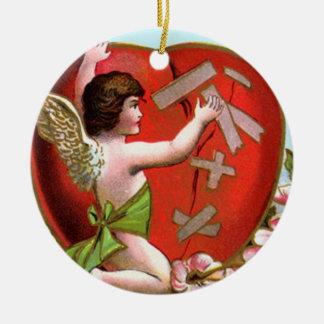 Cupid que repara el corazón quebrado adorno redondo de cerámica