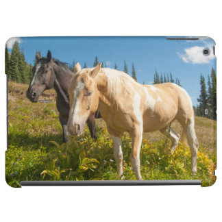 Curious horses foraging on grass iPad air case