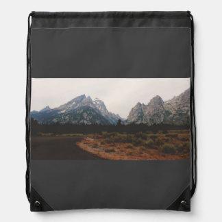 Curva en un camino lejos de la montaña mochilas