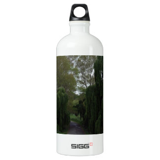 Curved road down a country lane lined green trees aluminum water bottle