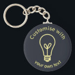 """Custom Light Bulb Icon Keychain<br><div class=""""desc"""">Simple and elegant light bulb icon,  symbolic of having a bright idea,  on dark blue background to customise with your own text.</div>"""