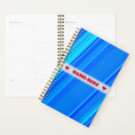 "Custom Name   Blue and Cyan Lines Pattern Planner<br><div class=""desc"">This planner design features a pattern with lines colored various shades of colors like blue and cyan. The front also features a custom name between two heart shapes in red-colored text, within a hazy light gray colored area. A planner like this might make a great personalized gift for a student...</div>"