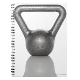 Cut out of a kettle bell on white background spiral notebook