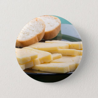 Cut slices of cheese on a plate close-up button
