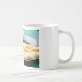 Cut slices of cheese on a plate close-up coffee mug