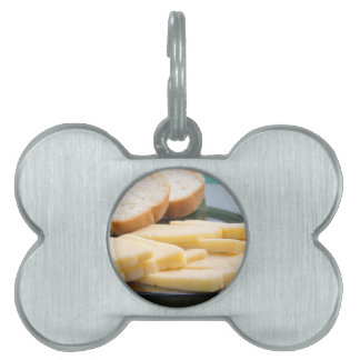 Cut slices of cheese on a plate close-up pet name tag