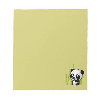 Cute black and white panda bear in a bamboo grove. note pad