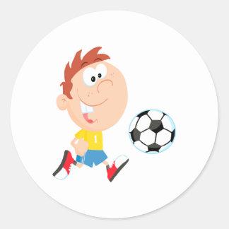 cute cartoon boy kicking soccerball classic round sticker
