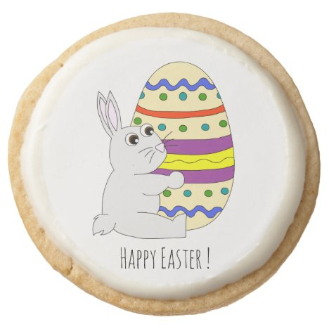 Cute easter bunny holding painted egg round shortbread cookie