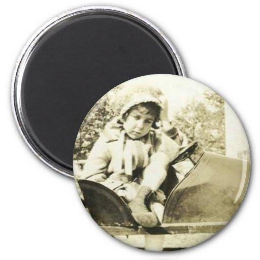 Cute girl in a peddle car round magnet