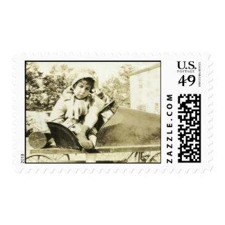 Cute girl in a peddle car stamp