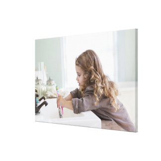 Cute little girl brushing teeth at bathroom sink stretched canvas print