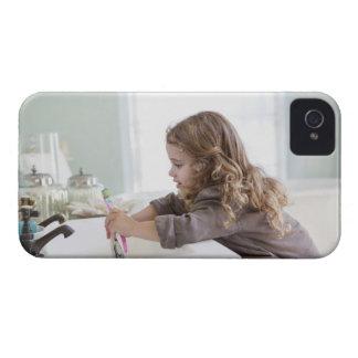 Cute little girl brushing teeth at bathroom sink iPhone 4 case