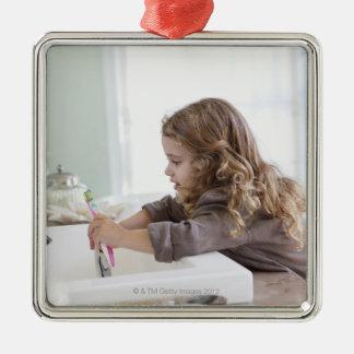 Cute little girl brushing teeth at bathroom sink metal ornament