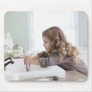 Cute little girl brushing teeth at bathroom sink mouse pad