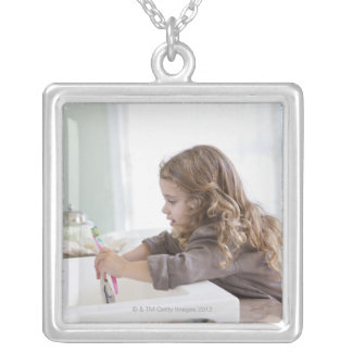 Cute little girl brushing teeth at bathroom sink silver plated necklace